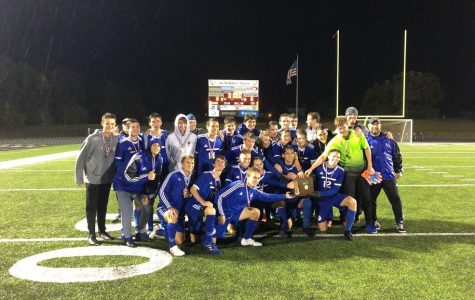 The boys soccer team crouches together to receive their CHL Championship plaque.