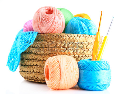 A basket full of colorful yarns alongside hooks that are useful for crocheting. PHOTO FROM:  www.caitlinsconatgiouscreations.com